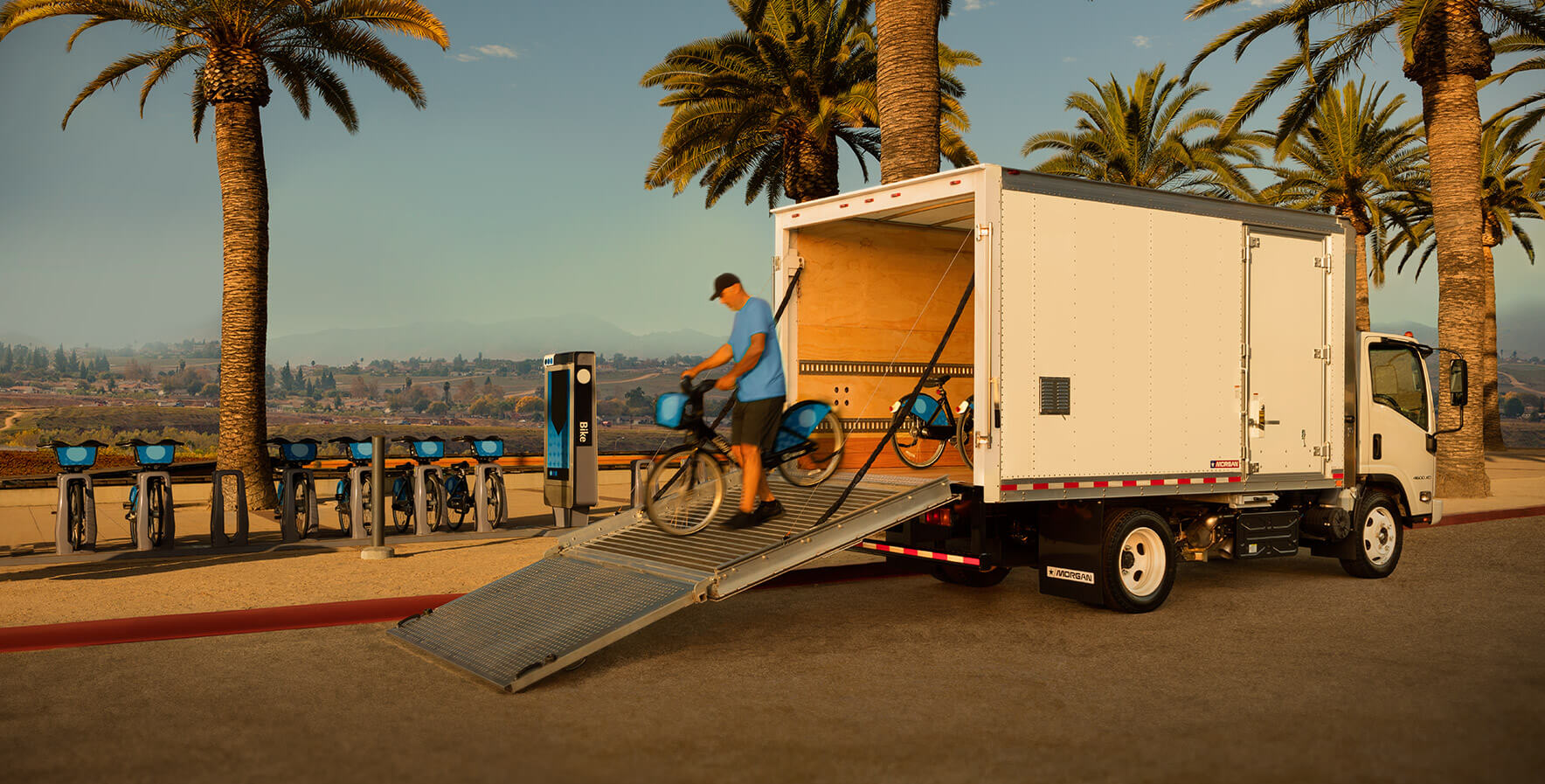 Dry Freight Proscape-Van man walking a ride-share bike down the ProScape-Van ramp